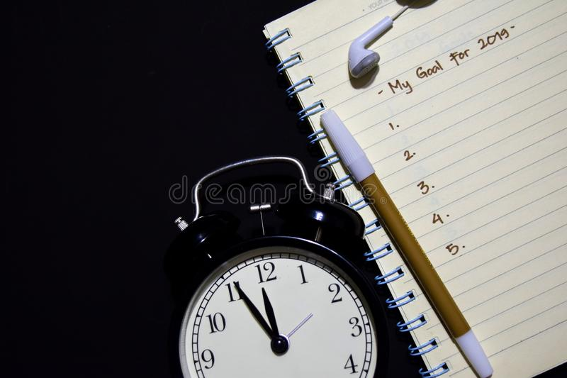 My Goal for 2019 text on notebook, alarm clock, color pen, earphone on black background, stock photos