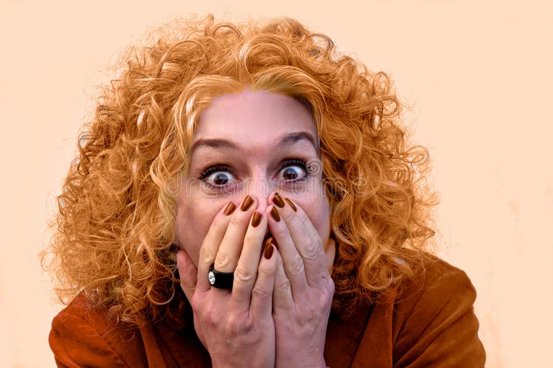 My god, I am orange. Shocked and frightened woman after looking in the mirror. Her hair has turned orange after dyeing