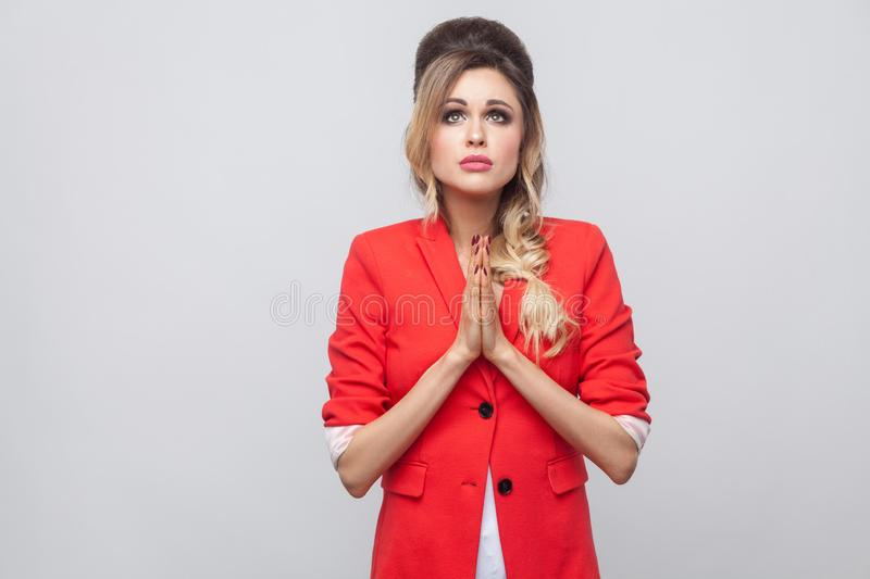 My God please forgive me. Pleading beautiful business lady with hairstyle and makeup in red fancy blazer, standing with palms hand. And looking up. indoor royalty free stock image