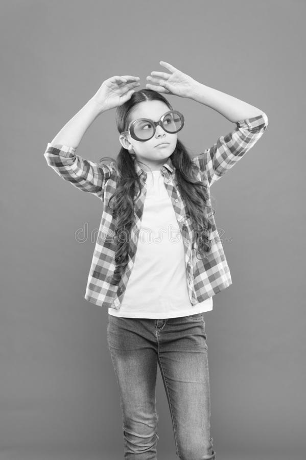 My goggles as unique as me. Adorable little girl wearing fancy goggles on orange background. Cute small child with royalty free stock photos
