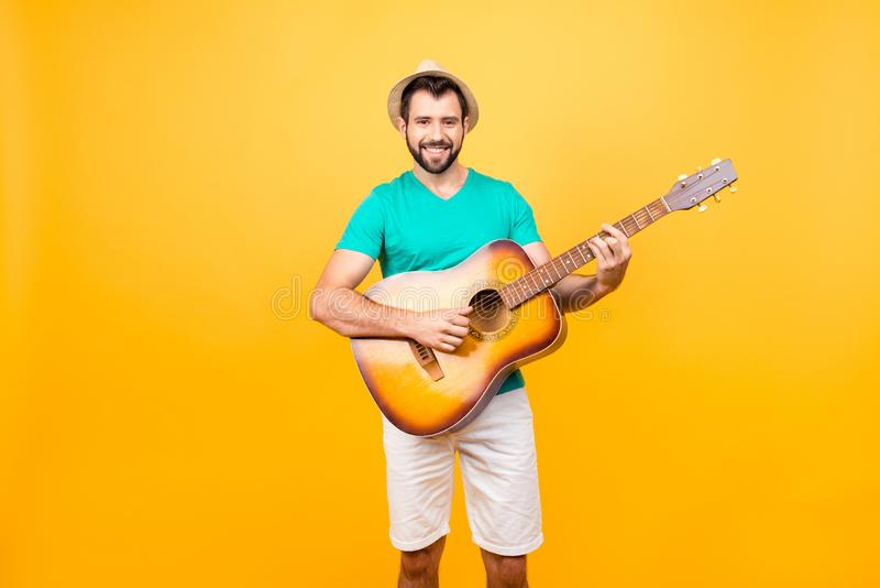 My guitar is my second soul! Portrait of smiling joyful funky glad positive guy with bristle, wearing tshirt and shorts, he is pl royalty free stock photos