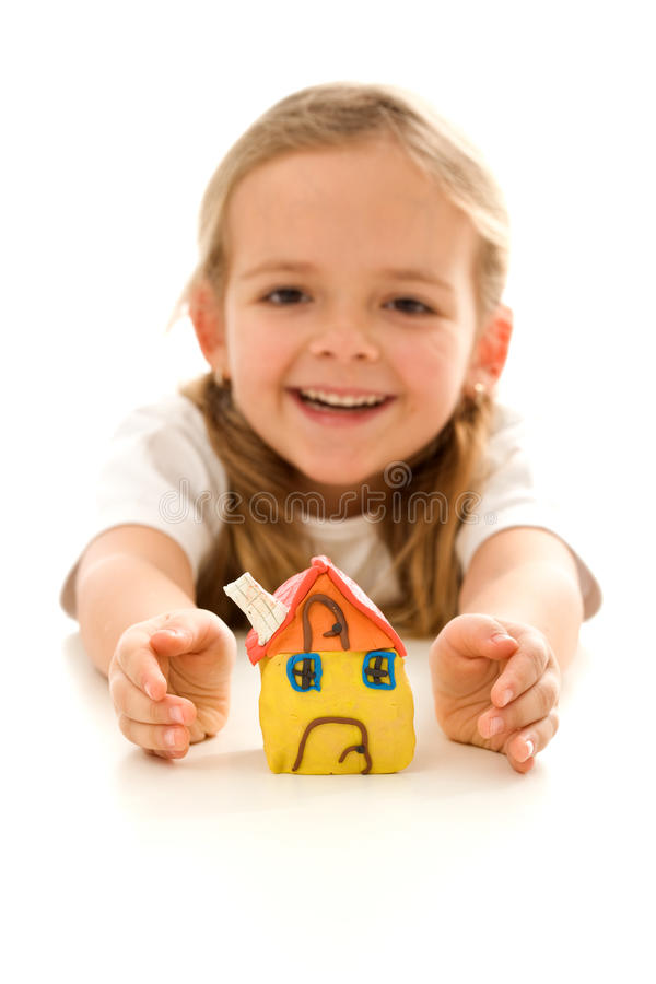My home is protected. Insurance concept with happy girl shielding her clay model house royalty free stock image