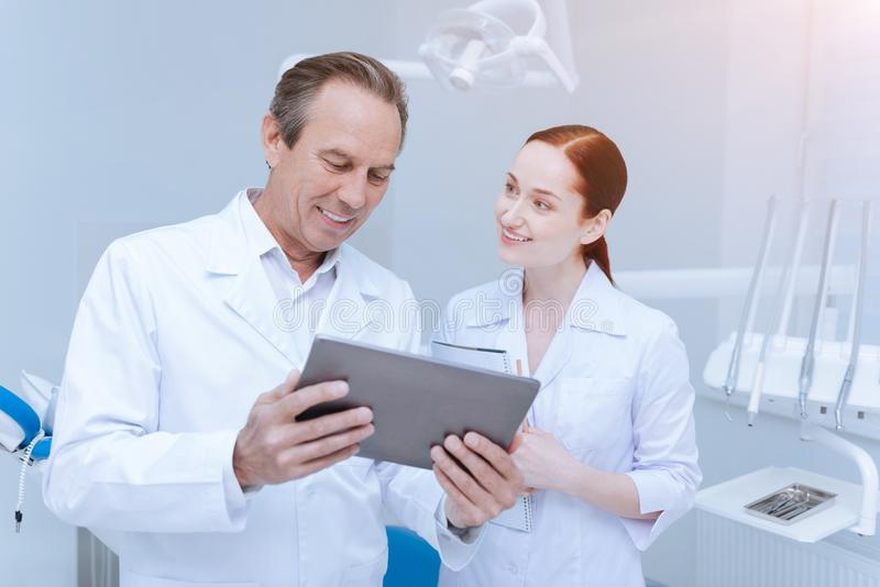 Competent stomatologist looking at screen of tablet stock images