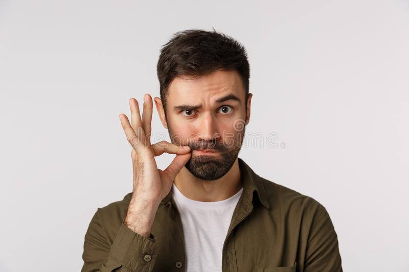 My lips are sealed with promise. Serious and funny bearded adult man keep mouth shut, making zip gesture and raise one stock photos