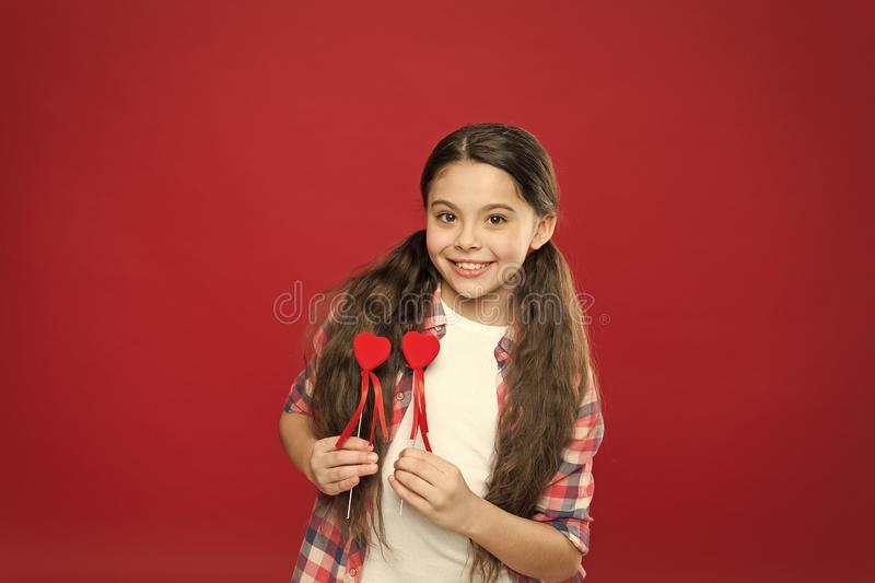 My love for you is forever. Small girl holding hearts on sticks. Cute girl with small red hearts. Small child with heart stock images