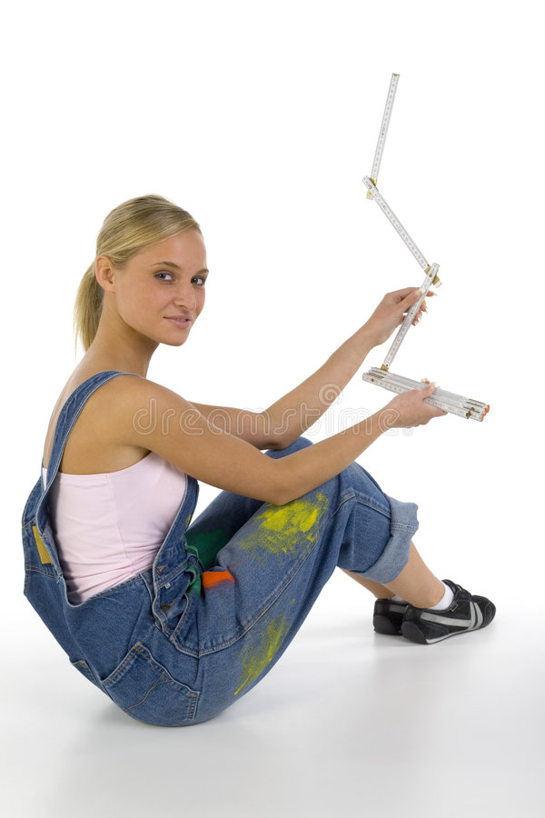 My measure. Young smiling blonde wearing dungarees with measure in hands. Sitting on floor. Looking at camera, white background stock image