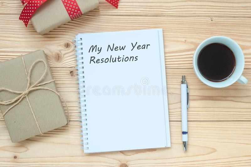 My New Year Resolutions word with notebook, black coffee cup and pen on wooden table, Top view and copy space. New Start, Goals, S. Olution, Strategy and Mission royalty free stock photography