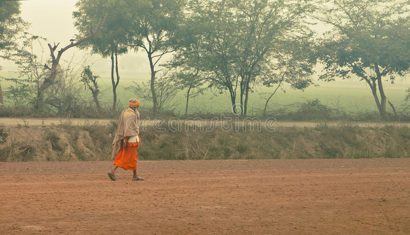 Uttar Pradesh, India - Jan 2017: Man is going through the empty field royalty free stock image