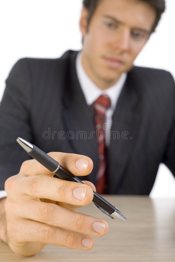 Is this my pen?. Young, handsome businessman. Seating behind desk and holding a pen. Looking at pen. White background, front royalty free stock photo