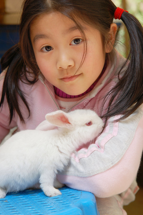 My pet. Little asian girl with the baby rabbit stock image