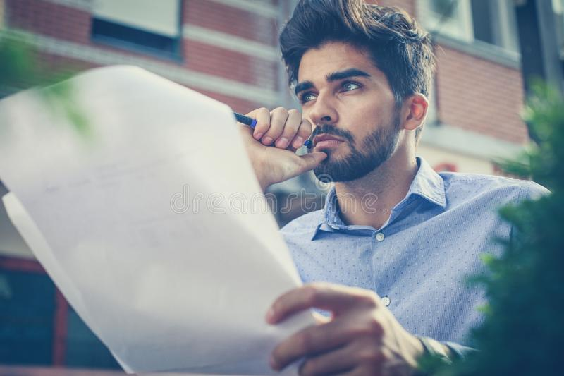 My plan must succeed. Business man in cafe street holding document and thinking. Close up stock image