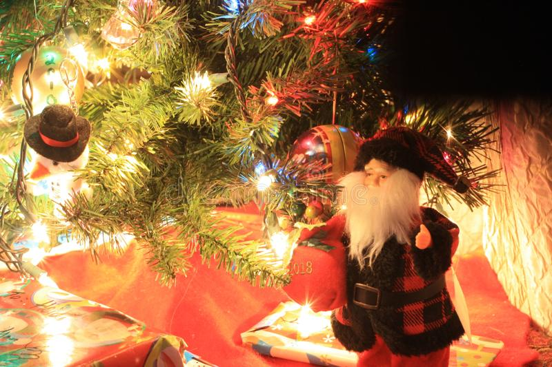 Santa Claus Doll Beneath the Tree. My Santa Claus doll with a harsh contrasting exposure. Could be useful for magazines, because it gives a strange emotive royalty free stock photography