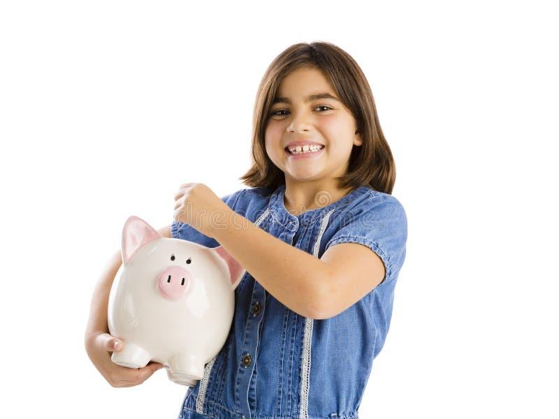 My savings. Young girl start her savings on a piggybank stock photography