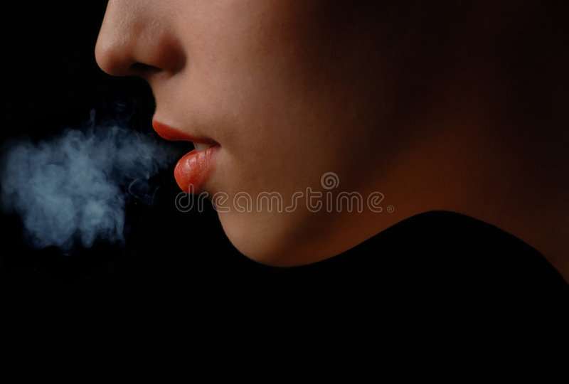 My smoke, my risk, my pleasure. Half-face of the smoking woman on a black background royalty free stock image
