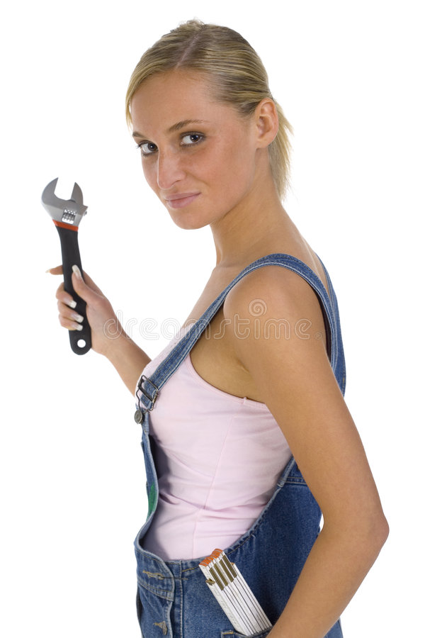 My spanner. Young blonde wearing dungarees with spanner in hand and measure in pocket. Isolated on white in studio. Looking at camera, side view stock photos