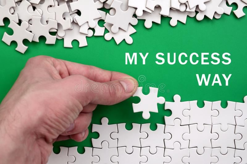 My success way. The hand folds a white jigsaw puzzle and a pile stock photos