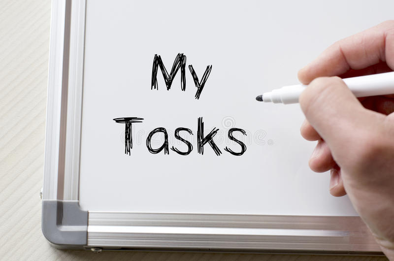 My tasks written on whiteboard. Human hand writing my tasks on whiteboard stock photo