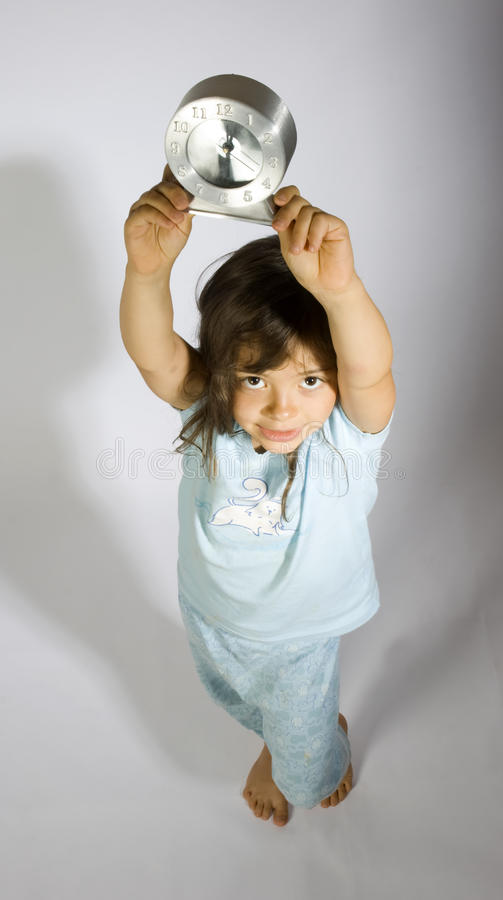 My time. Baby child with pyjamas and silver clock royalty free stock image