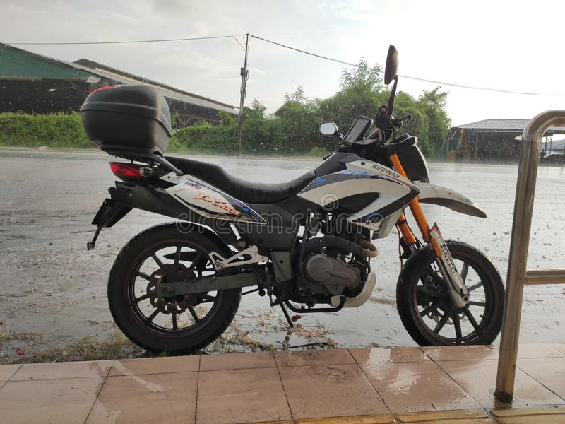 My very own keeway Tx200g in Malaysia. A quick stop under the rain. My very own keeway Tx200g in Malaysia. A quick stop under the stock photo