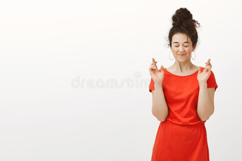 My wish definitely come true. Grinning happy european girl in red dress with hair combed in bun, closing eyes and royalty free stock photos