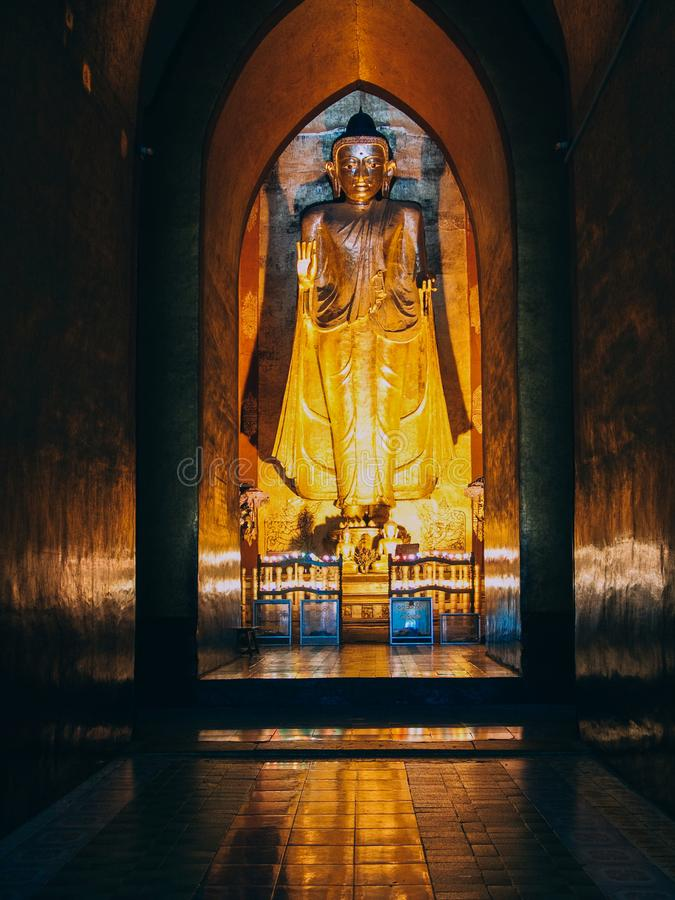 Myanmar, Bagan - giant Buddha inside of Pagoda, ambient light.  royalty free stock photography