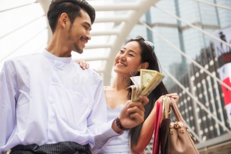 Myanmar couple shopping in city. Happy Myanmar couple shopping in city with many money banknotes, US dollar bills. Burmese Businessman with longyi dress take his royalty free stock image