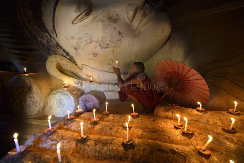 Myanmar - Januari 24, 2017: Lite Myanmar ber den buddistiska novismunken framme av Buddhastatyn på pagoden, Bagan arkivbilder