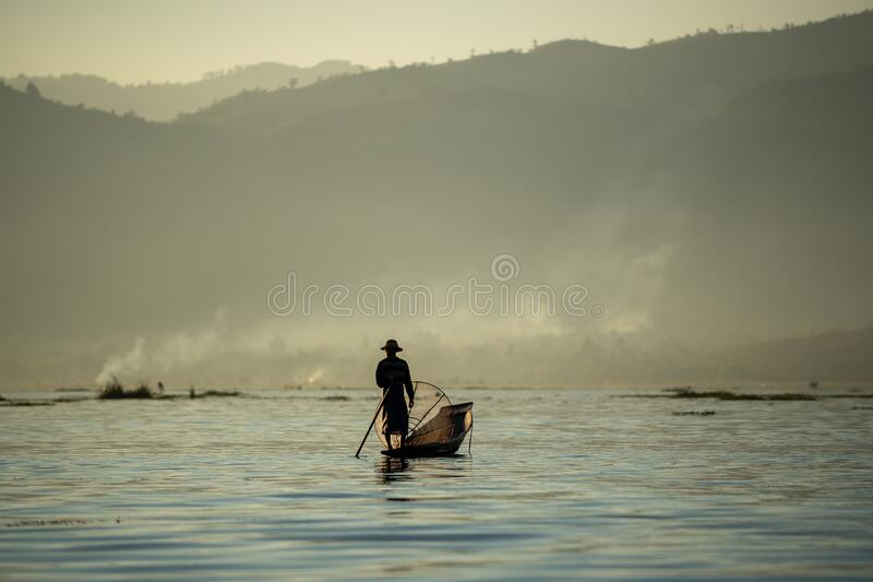 Myanmar men rowing boats using legs Came out to fish in the morning with fog and smoke. Background in the mountains in Inle Lake, Myanmar stock images