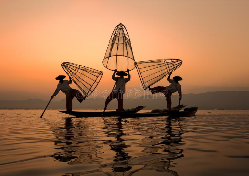 Myanmar travel attraction landmark - Traditional Burmese fishermen with fishing net at Inle lake in Myanmar famous for their dist stock images