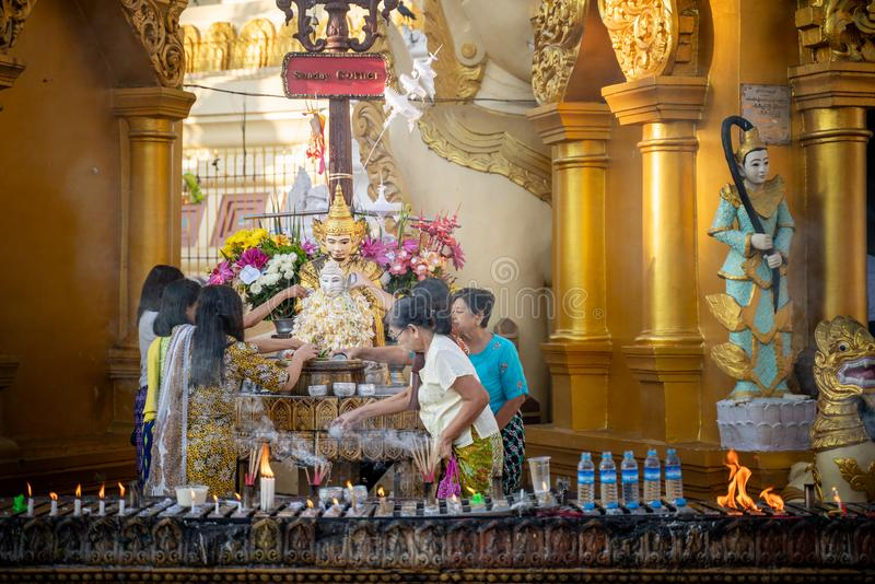 Myanmar, Yangon, November 2019, Shwedagon Pagoda, local people pour water on the buddha and  pray during a traditional Buddhist royalty free stock image