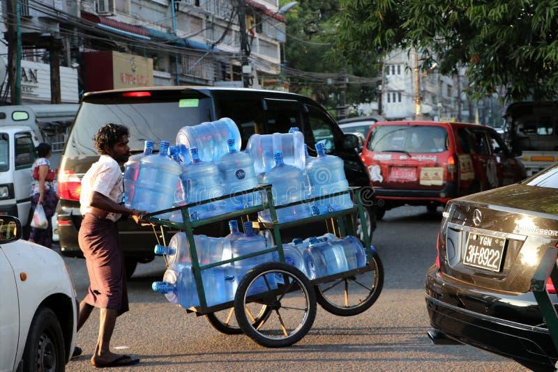 Myanmese-Arbeitskraftmann, der das Rad drei des Wassertankerkarrens auf der Straße in Rangun drückt lizenzfreie stockfotos