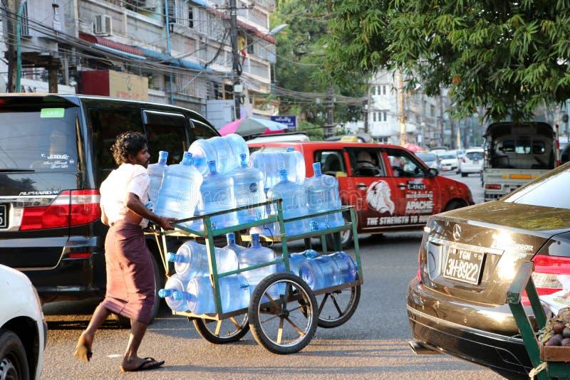 Myanmese-Arbeitskraftmann, der das Rad drei des Wassertankerkarrens auf der Stra?e in Rangun dr?ckt lizenzfreies stockbild