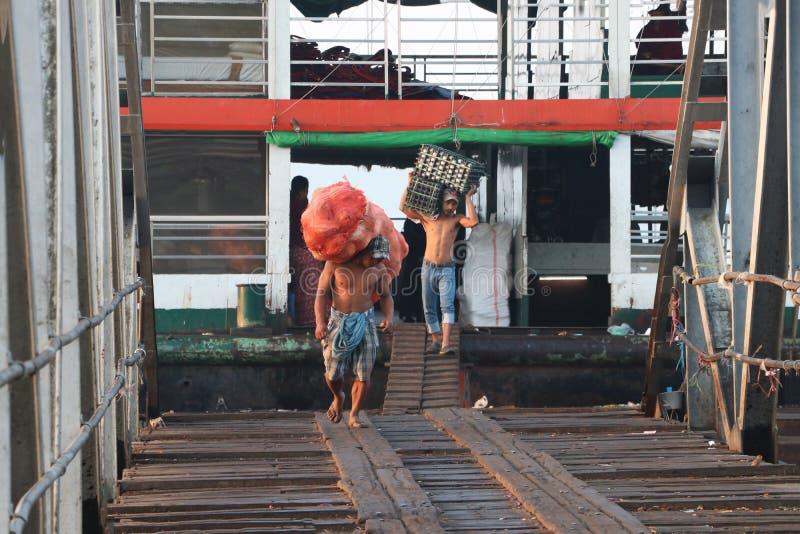 Myanmese arbetare bär den stora påsekokosnöten, och andägg i en spjällåda landsätter från skeppet och går förbi bron av arkivbilder