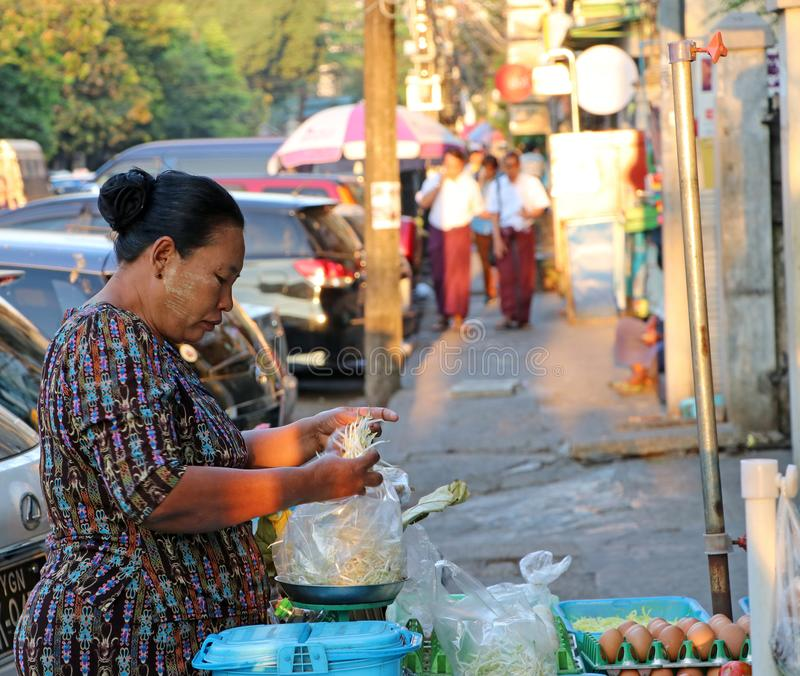 Myanmese female street vendor selling vegetable is weighing bean sprouts at her shop beside road in Yangon royalty free stock images