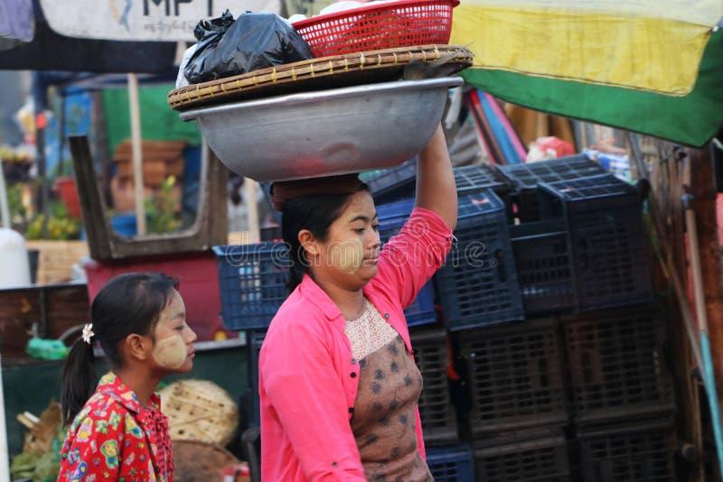 Myanmese kobieta z thanakha Myanmar proszkiem na jej twarz stawiającym duży aluminium emaliującym basenie na jej głowie przynosić zdjęcia stock
