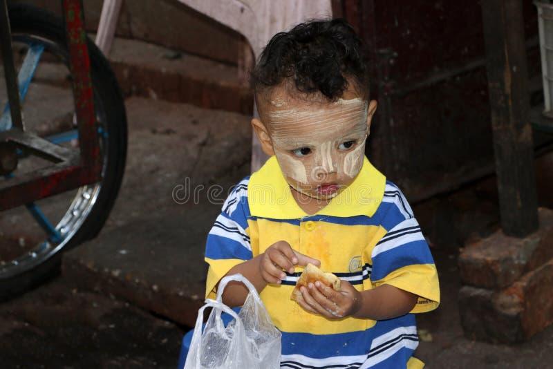 Myanmese pojke med thanakha på framsidan som Deliciously äter efterrätten royaltyfri bild