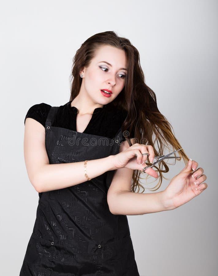 Mycket attraktiv och stilfull yrkesmässig frisörkvinna med sax i assistent frisörkvinnan uttrycker royaltyfri bild