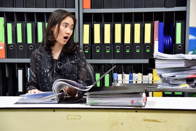 Mycket begrepp för arbete och för hårt arbete, asiatisk kontorsarbetare som är chockad om lott av skrivbordsarbete arkivbilder