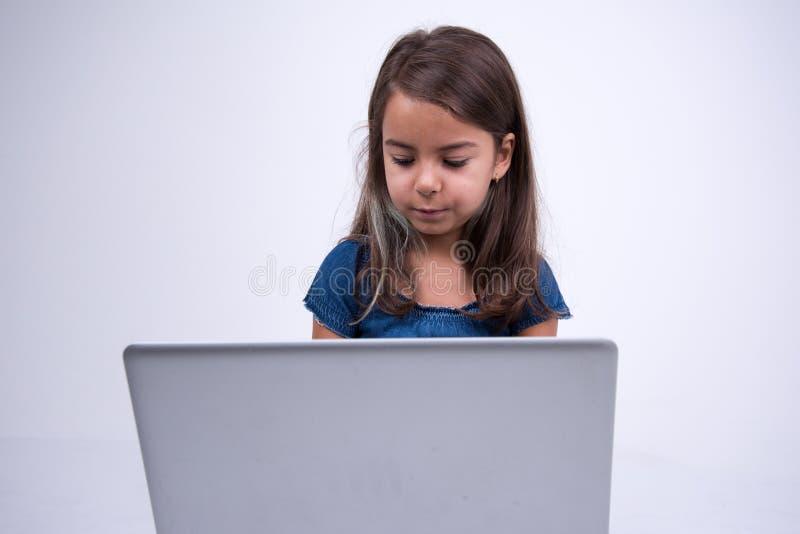 Mycket besviken liten flicka att se något i anteckningsboken arkivfoton