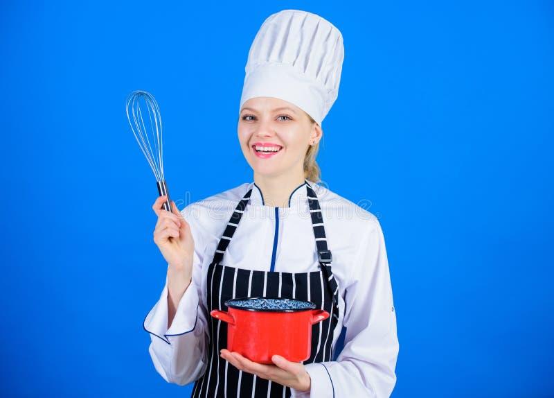 Mycket enkelt att använda Den yrkesmässiga kocken som ler med krukan, och tråd viftar Den gulliga kökhembiträdet med rostfritt st arkivfoton