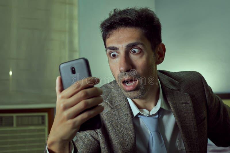 Mycket förvånad man som ser hans smartphone i ett rum royaltyfri bild