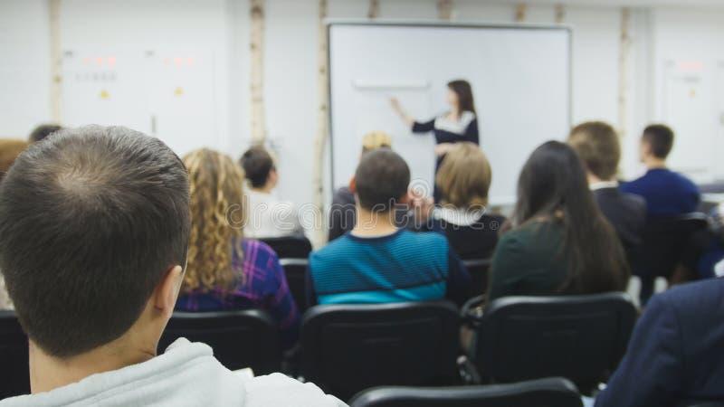 Mycket folk som sitter på ett seminarium, föreläser och konferenser - affärsmän och IT-professionell arkivfoto