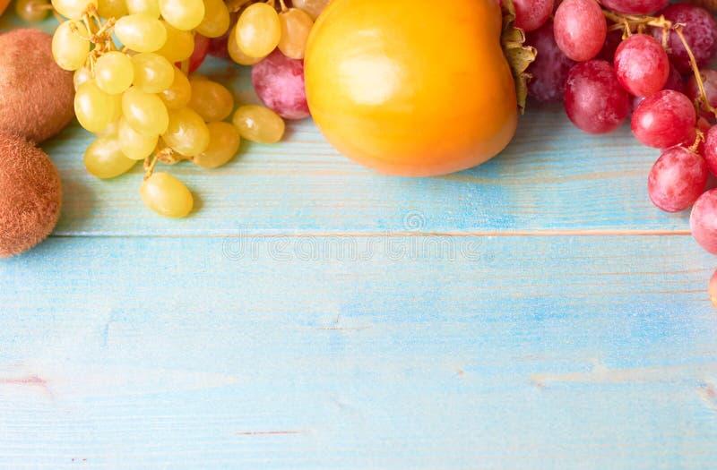 Mycket frukt på en blå träbakgrund arkivbild