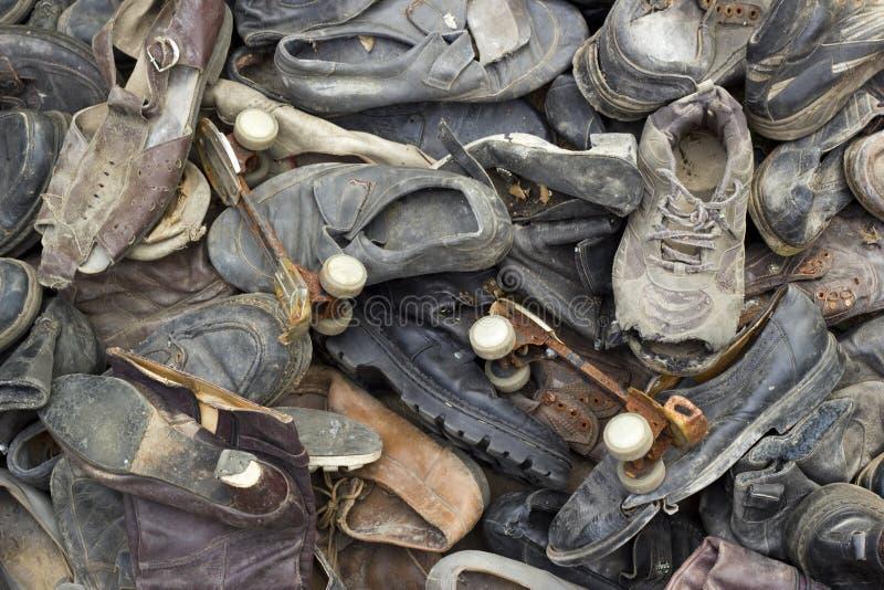 Mycket gamla avfallskor med par av rostig rullskridskor arkivfoton