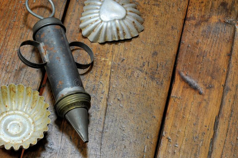 Mycket gamla bakelsehjälpmedel: kakor injektionsspruta och kakaskärare slitage bakgrundsträ royaltyfri bild