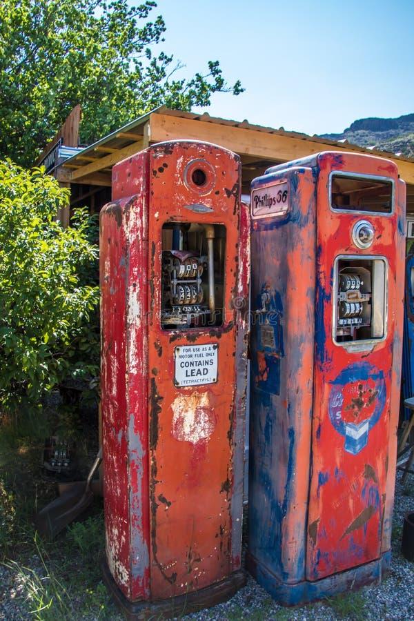 Mycket gamla bensinpumpar bredvid en väg för 2 gränd i mitt av ingenstans royaltyfri foto