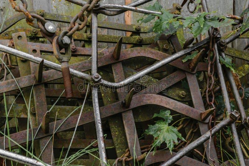 Mycket gamla och rostiga harv förlägger nära ladugårdväggen på bygd arkivfoto
