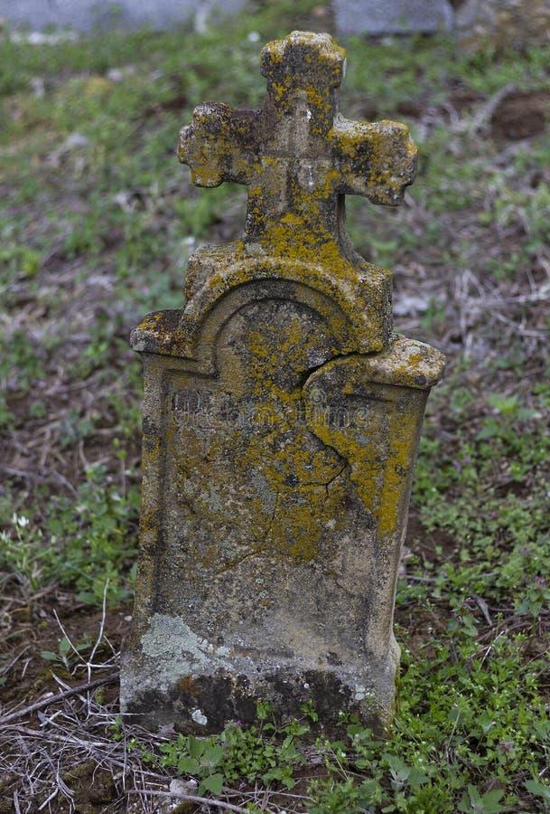 Mycket gammal gravsten i en kyrkogård arkivbilder