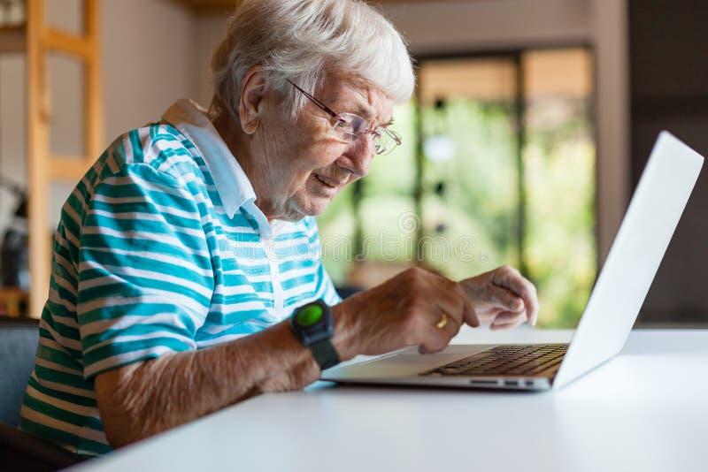 Mycket gammal hög kvinna som använder en dator arkivfoton
