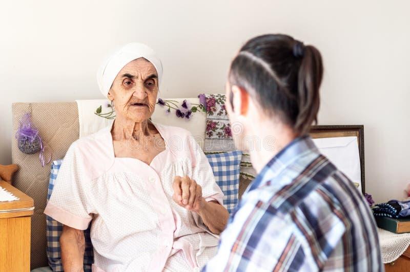 Mycket gammal hög kvinna som har en konversation med hennes sonson arkivfoton